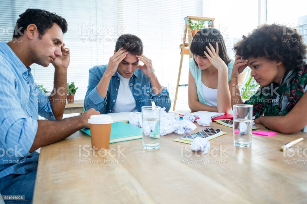 Exhausted creative business team riled up stock photo