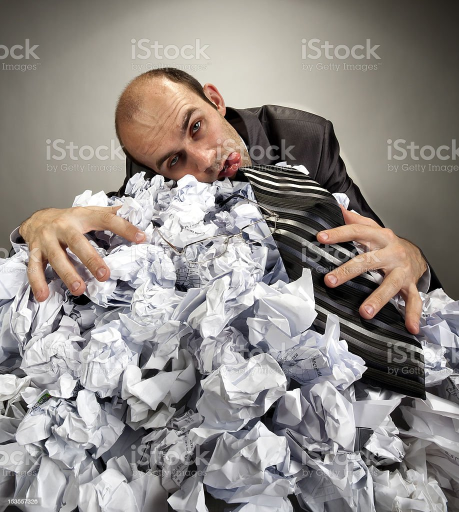 Exhausted depressive businessman laying on crumpled papers royalty-free stock photo