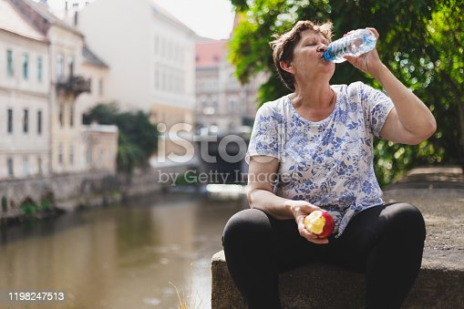104545719istockphoto Exhausted granny holding a fruit in one hand while drinking from water bottle with the other 1198247513