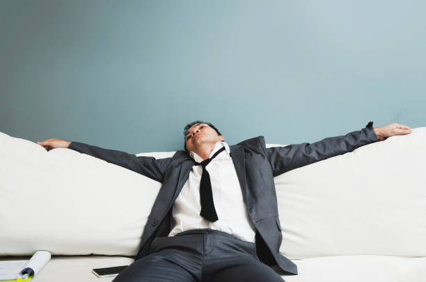 exhausted, illness, tired, stressed from overworked concepts. businessman in grey suit sit on sofa. senior man sleepy. - divano procrastinazione foto e immagini stock