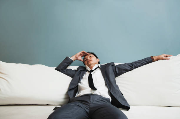 exhausted, illness, tired, stressed from overworked concepts. businessman in grey suit has headache from migraine. - divano procrastinazione foto e immagini stock