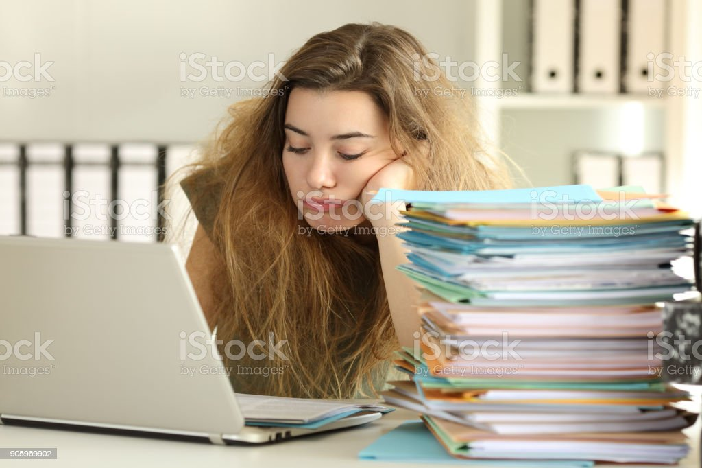 Exhausted intern with tousled hair working at office stock photo