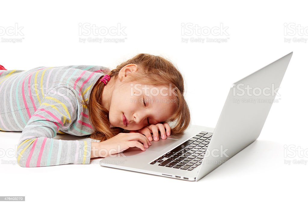 Exhausted little girl sleeping on laptop keyboard stock photo