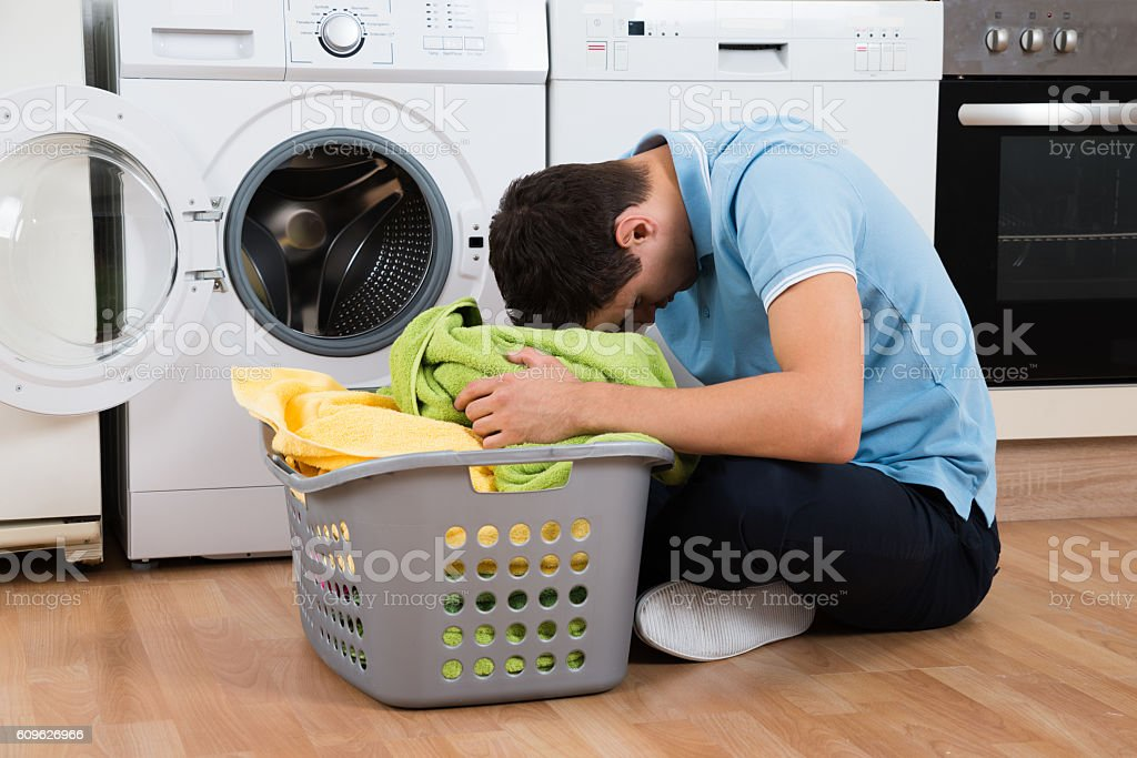 Exhausted Man With Laundry Basket Sitting By Washing Machine stock photo