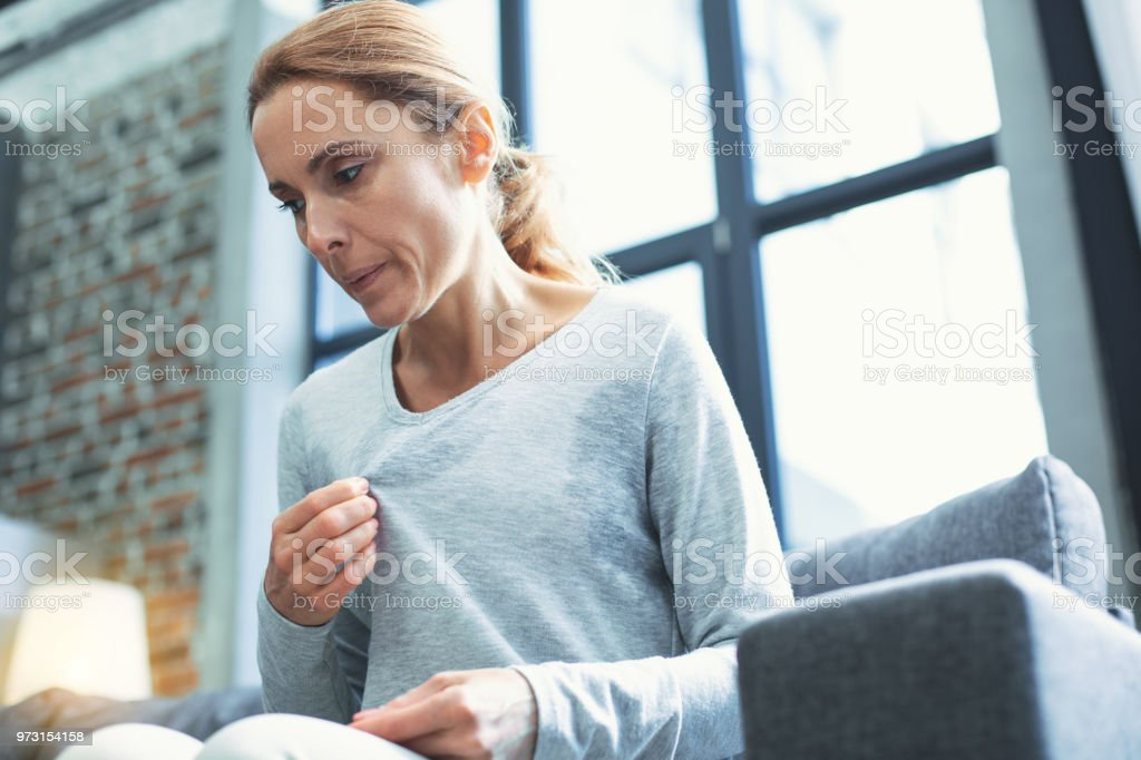 Exhausted mature woman entering menopause stock photo