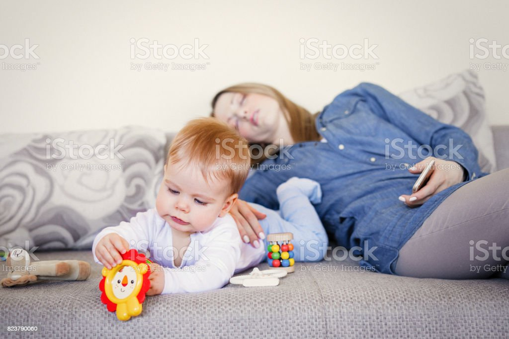 Exhausted mother and baby on the couch stock photo