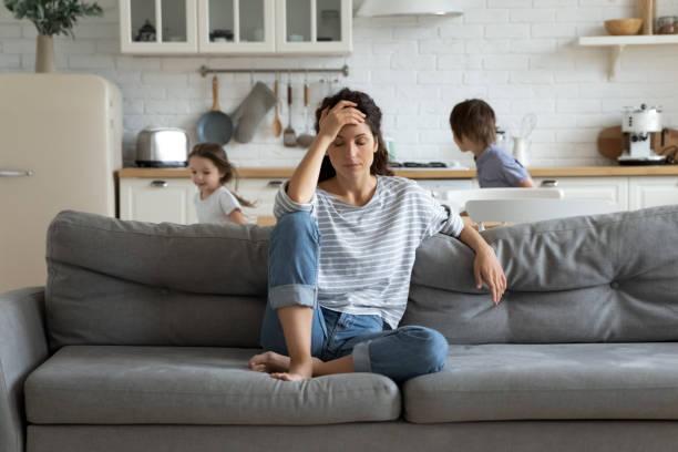 Erschöpfte Mutter sitzt auf der Couch, während Kinder zu Hause laufen – Foto