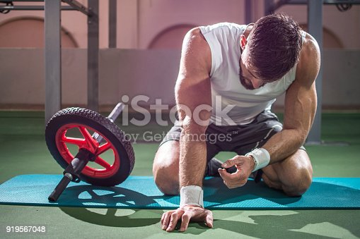 istock Exhausted muscular man taking break from working out with ab wheel at gym. 919567048