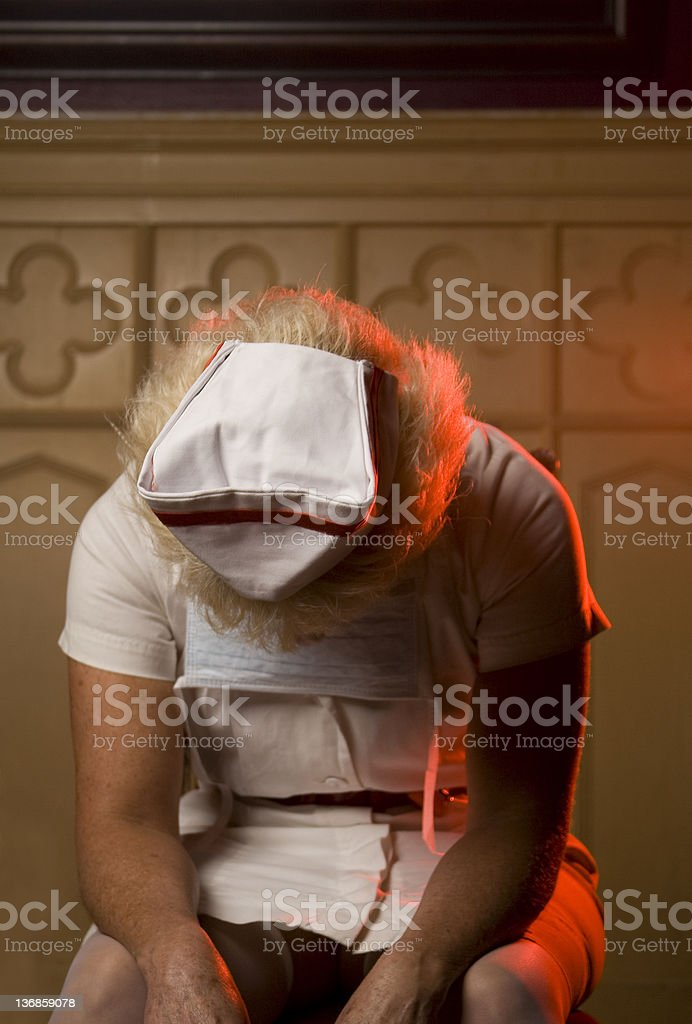 Exhausted Nurse Slouches In A Chair An exhausted nurse slouches in a chair with visible red light from an ambulance. 50-54 Years Stock Photo