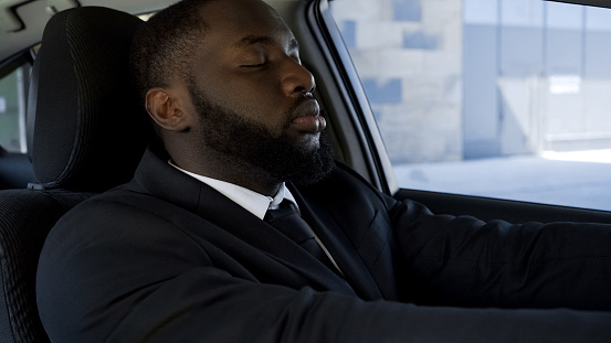 istock Exhausted of active way of life black man falling asleep in car, tired of work 975785882