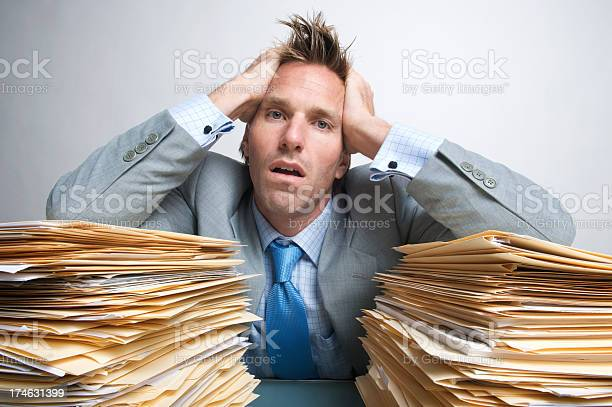 Exhausted Office Worker Businessman Holding Head In Hands On Folders Stock Photo - Download Image Now