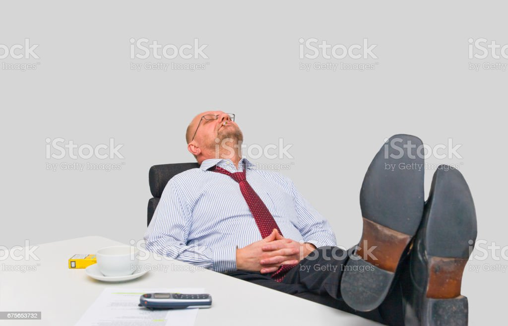 Exhausted office worker taking a nap Exhausted office worker taking a nap on his desk Adult Stock Photo
