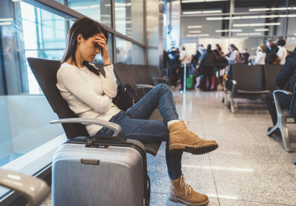 Exhausted passenger at the airport Young woman napping at the airport departure area while waiting for the flight jet lag stock pictures, royalty-free photos & images
