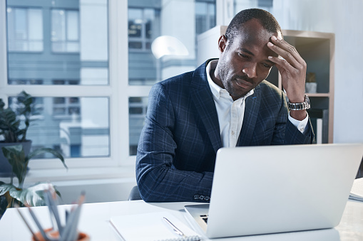Exhausted Pensive Employee Is Using Smart Gadget Stock Photo - Download Image Now