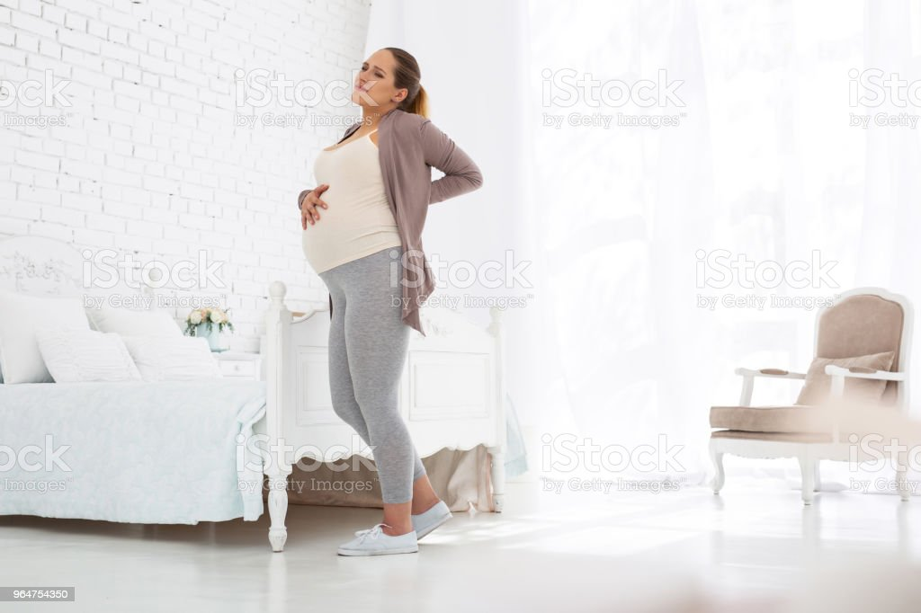 Exhausted pregnant woman suffering from back pain royalty-free stock photo