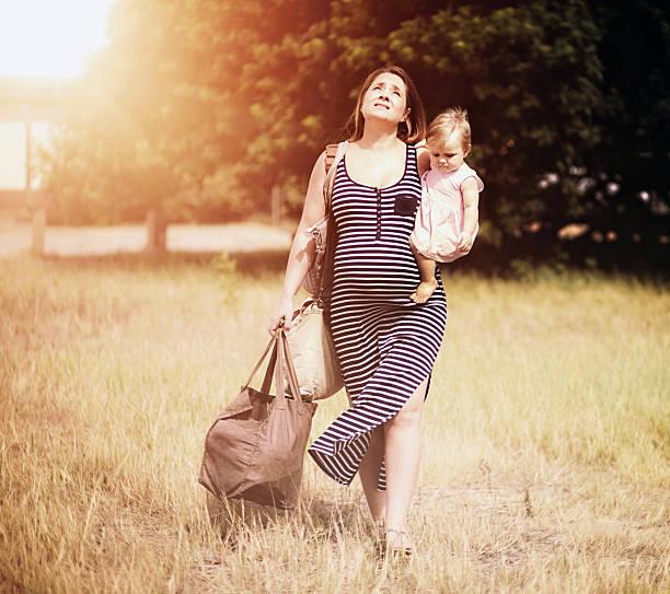 ziemlich schwangere frau mit kleinkind stapfen durch warme sonne - kleinkind busy bags stock-fotos und bilder
