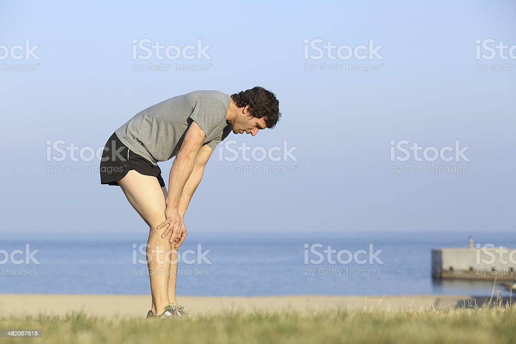 Exhausted runner man resting on the beach after workout stock photo