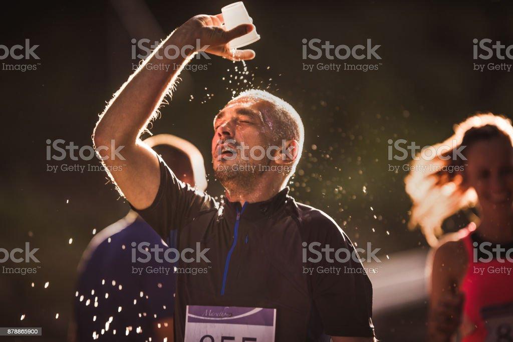 Erschöpft Läufer Gießen von Wasser auf dem Kopf beim Marathon-Lauf in der Natur. – Foto