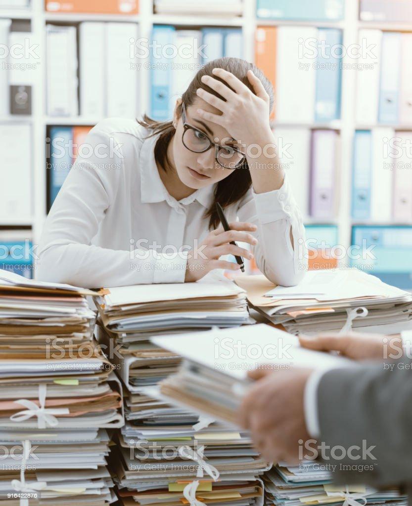 Secretário exausto, sobrecarregado com trabalho - foto de acervo