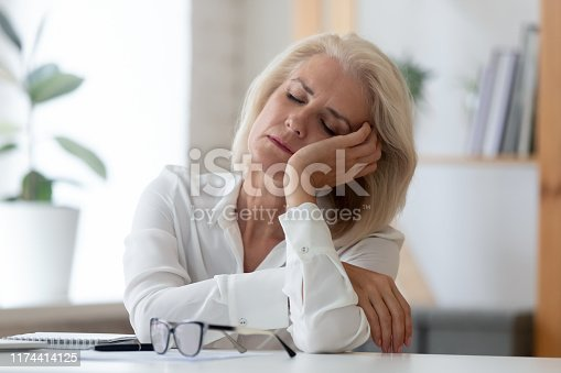 istock Exhausted senior businesswoman fall asleep at workplace 1174414125