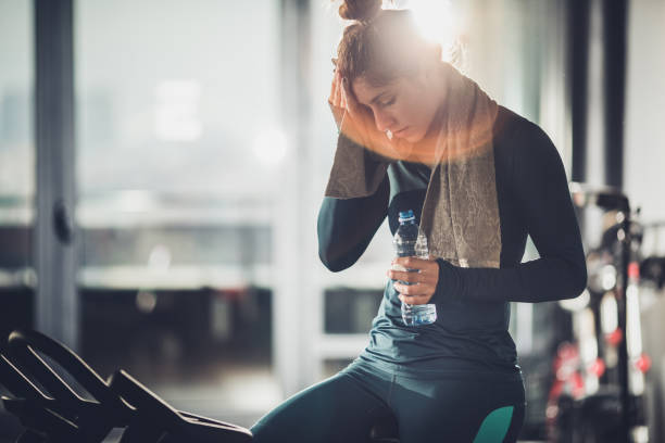 Exhausted sportswoman having a water break during exercising class in a gym. Tired sweaty woman taking a break after exercising on a stationary bike in a health club. groyne stock pictures, royalty-free photos & images