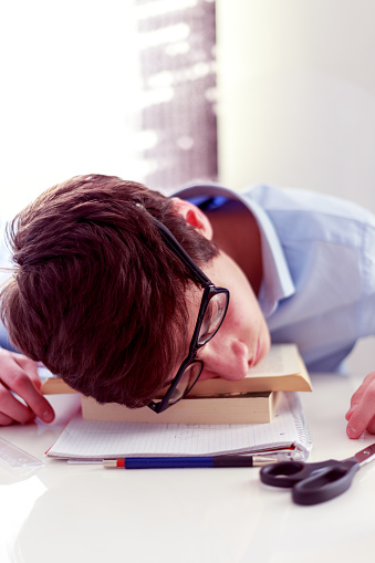 Exhausted student fell asleep on the books