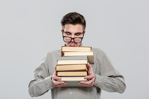 istock Exhausted student in glasses holding books 496632100