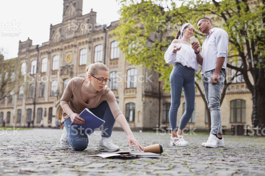 Exhausted student picking her notebooks from the ground royalty-free stock photo