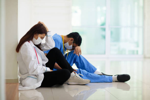 Exhausted tired doctor or nurse. Virus outbreak. stock photo