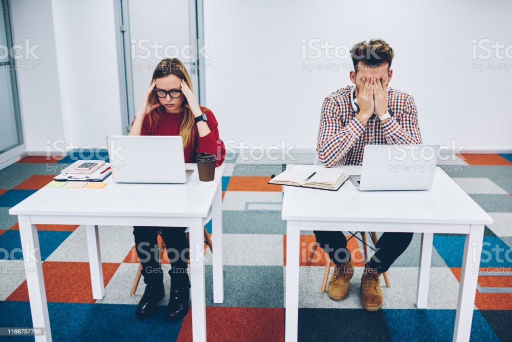 Exhausted two students preparing for upcoming exams at modern laptop...