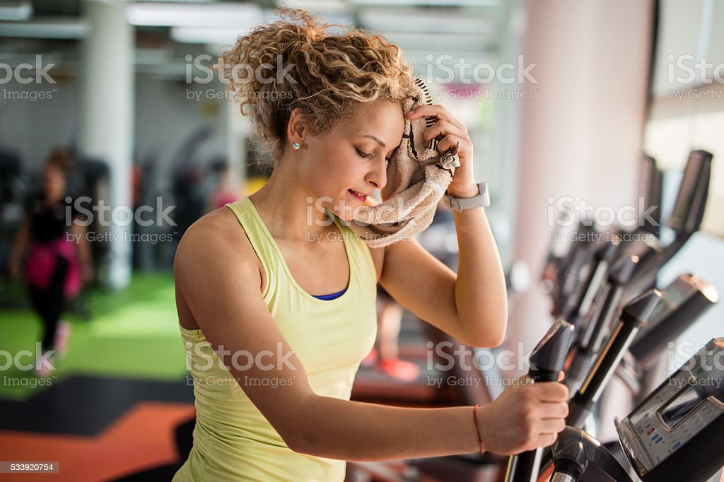 Exhausted woman wiping sweat with a towel in a gym. stock photo