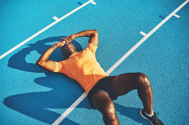 exhausted young athletic lying on a running track after training - esaurimento foto e immagini stock