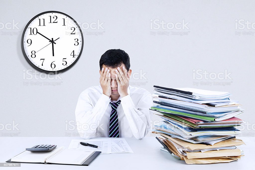 Exhausted young businessman stock photo