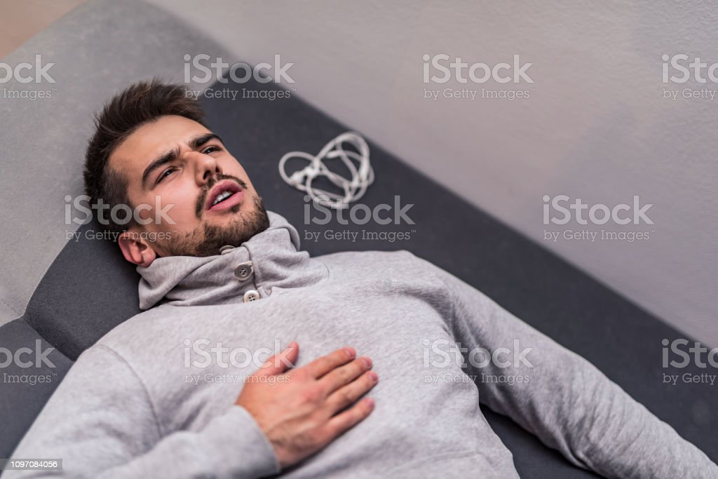 Exhausted young man having heart problems after a workout. stock photo