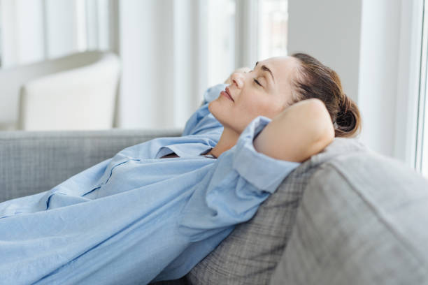 Exhausted young woman relaxing on a sofa stock photo