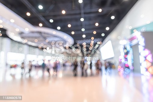 Exhibition event hall blur background of trade show business, world or international expo showcase, tech fair, with blurry exhibitor tradeshow booth displaying product with people crowd