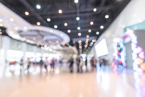 展示会イベントホールぼかしトレードショービジネスの背景 世界または国際的なエキスポショーケース テックフェア ぼやけた出展者トレードショーブースで人々の群衆と製品を表示 - からっぽのストックフォトや画像を多数ご用意