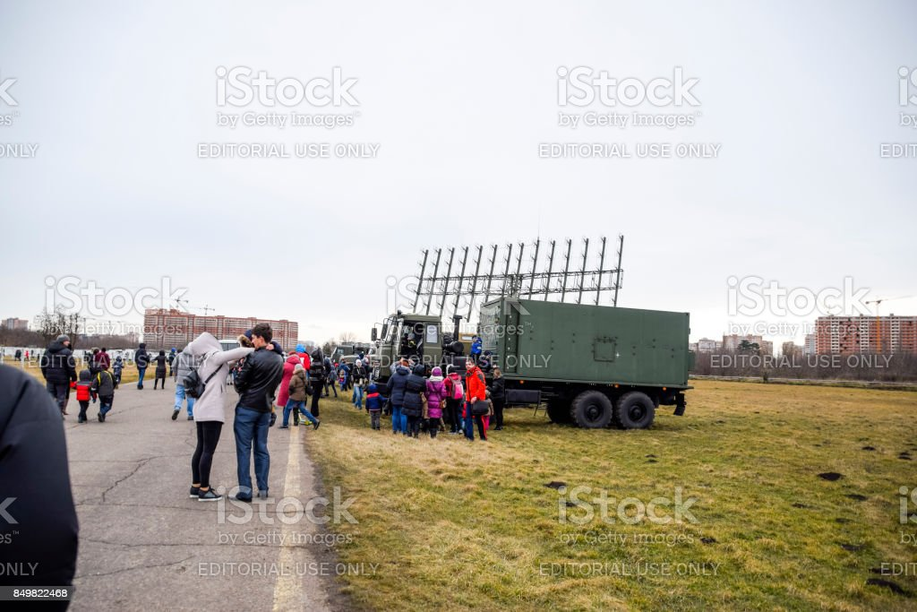 Exhibition of military equipment at the Krasnodar airfield. Viewers inspect Military cars and a mobile radar station. stock photo