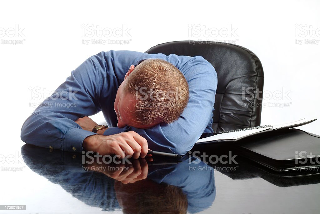 Exhuasted Businessman Asleep at His Desk stock photo