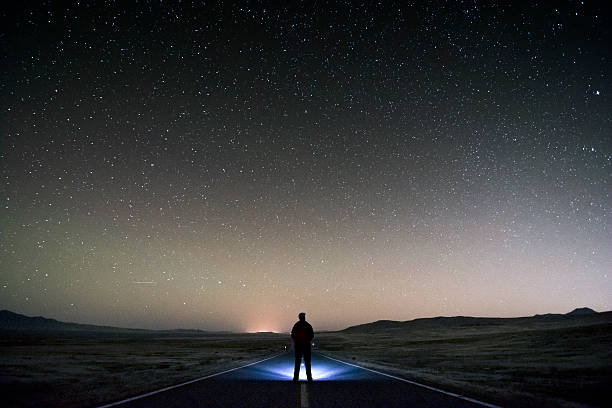 Existentialism Lonely man standing in the middle of the road on the desert looking into the stars in search of the answer to ultimate question regarding his and mankind existence. High ISO at 3200. middle of the road stock pictures, royalty-free photos & images