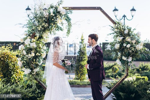 Exit ceremony of lovers in a hotel near the sea on the background of an arch of fresh flowers