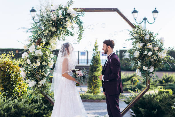 Exit ceremony of lovers in a hotel. Exit ceremony of lovers in a hotel near the sea on the background of an arch of fresh flowers natural arch stock pictures, royalty-free photos & images
