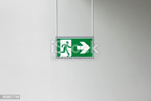 Closeup of modern illuminated emergency exit sign .