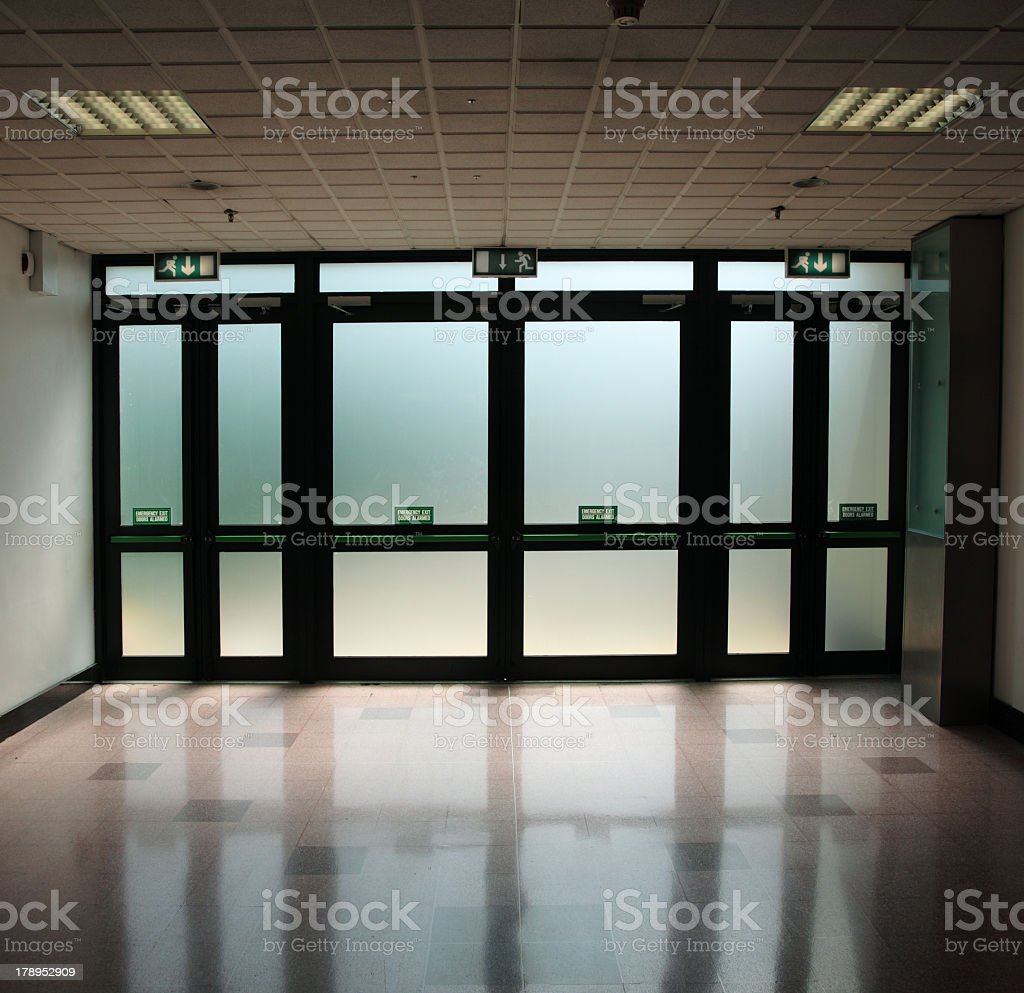 Exit signs above glass doors in a dimly lit hallway stock photo