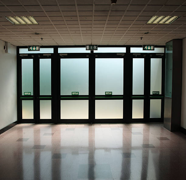 exit signs above glass doors in a dimly lit hallway - dimly stock pictures, royalty-free photos & images