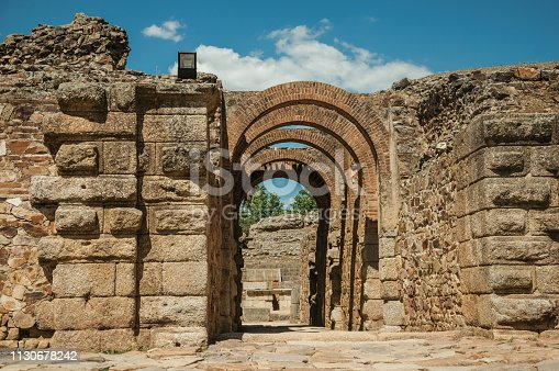 Exit gateway with arches of Roman Amphitheater in a sunny day, at the huge archaeological site of Merida. Founded by ancient Rome in western Spain, the city preserves many buildings of that era.