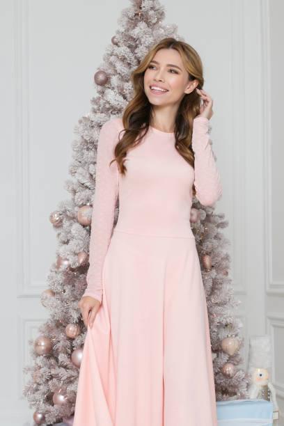 986e8d9b3 Exiten mujeres en un vestido largo rosa de pie cerca de árbol de Navidad  con regalos