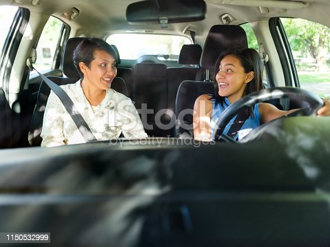 A front view photo of a female teenager sitting in a car next to her mother with an exited expression on her face as she looks at her before learning how to drive.