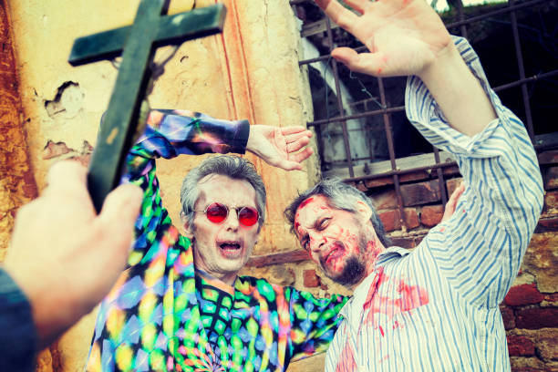 exorcism with a crucifix on two zombies in the cemetery stock photo