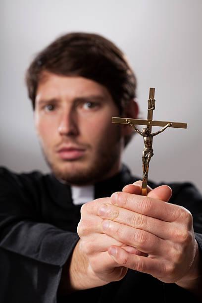 Exorcist with crucifix stock photo